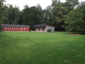 Große Lager-Spielwiese mit Blick vom Lärmschutzdamm zum Heim